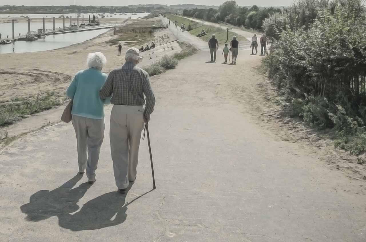 pareja de abuelos caminando y grupos de personas delante