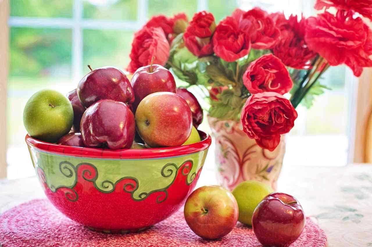 flores rojas y frutero con manzanas rojas y verdes