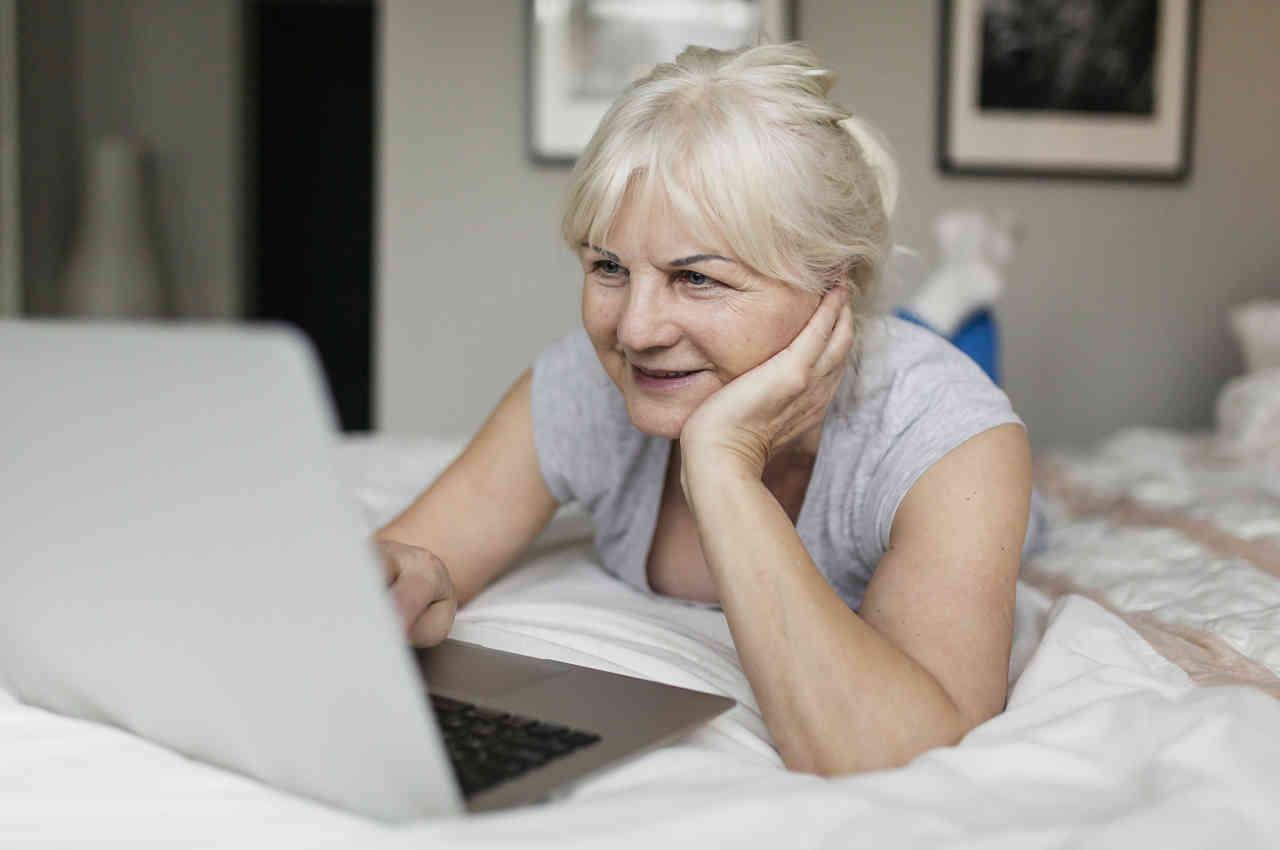 Señora recostada aprendiendo cómo buscar en google en su computador